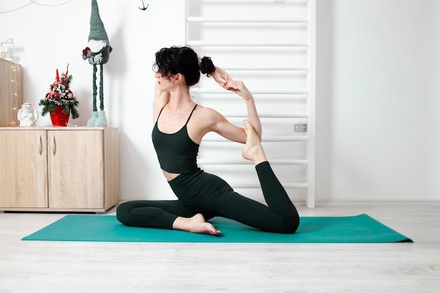 Jeune femme exerçant le yoga dans son propre appartement et profiter de sa journée