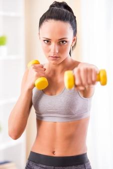 Jeune femme exerce avec des haltères à la maison.