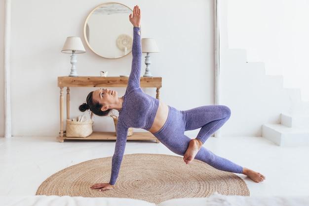 Jeune femme exerce à la maison. elle fait l'exercice de planche pour un ventre plat.