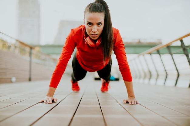 Jeune femme exerce sur la promenade après avoir couru le matin