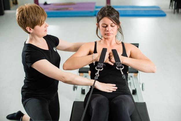 Jeune femme, exercice, sur, pilates, appareil, reformer, à, instructeur, à, gymnase