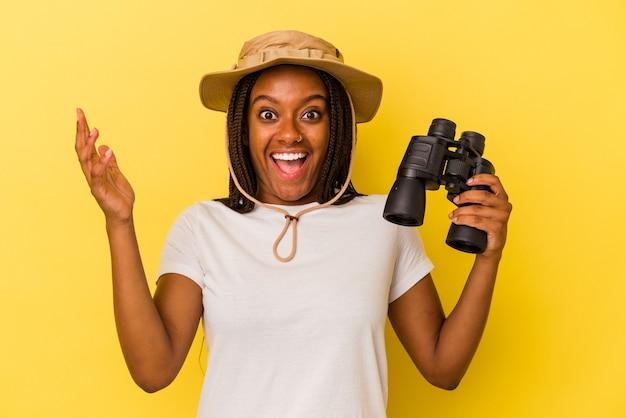 Jeune femme exploratrice afro-américaine tenant des jumelles isolées sur fond jaune recevant une agréable surprise, excitée et levant les mains.