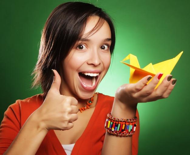 Jeune femme d'expression avec l'oiseau de papier au-dessus du vert