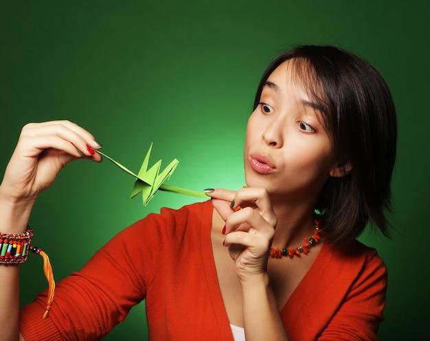Jeune femme d'expression avec un oiseau en papier sur un mur vert