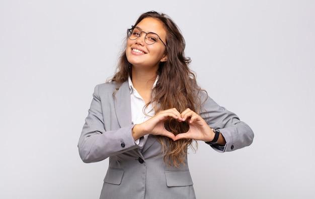 Jeune femme expressive avec des lunettes et un costume élégant posant sur un mur blanc