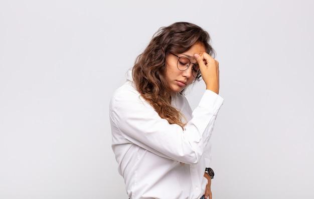 Jeune femme expressive avec des lunettes et un élégant chemisier blanc posant sur un mur blanc