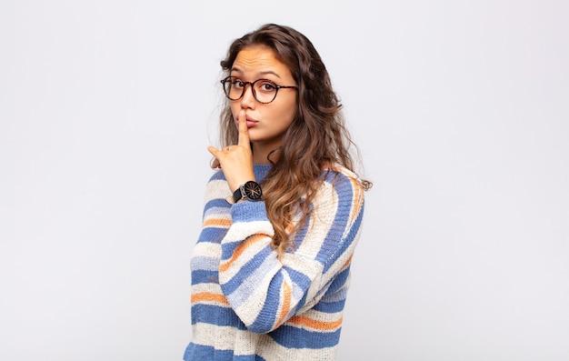 Jeune femme expressive avec des lunettes posant sur un mur blanc