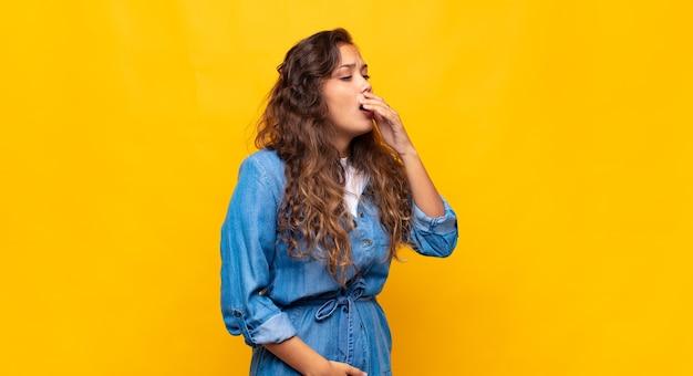 Jeune femme expressive posant sur un mur jaune