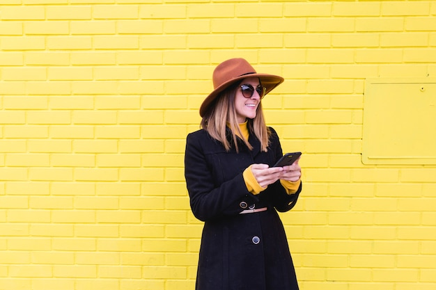 Jeune femme à l'extérieur à l'aide de téléphone portable et souriant. mode de vie en ville. mur de brique jaune