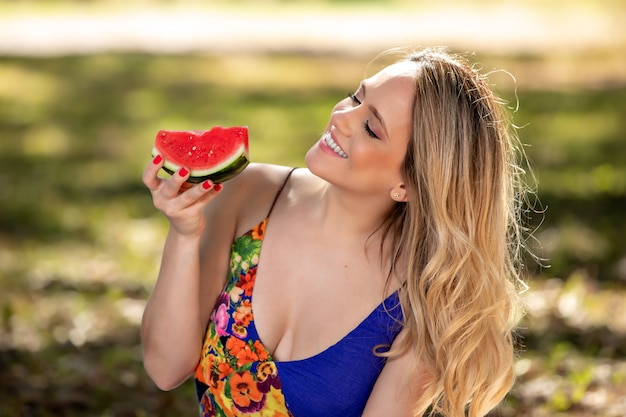 Jeune femme à l'extérieur sous les arbres dans un parc, heureuse et souriante, faisant du pique-nique et dégustant la pastèque.