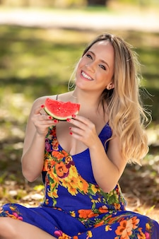 Jeune femme à l'extérieur sous les arbres dans un parc, heureuse et souriante, faisant pique-nique et dégustation de pastèque.