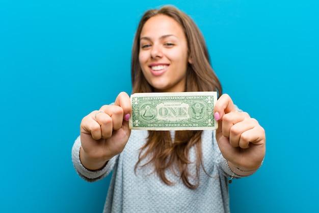 Jeune femme avec des factures sur fond bleu