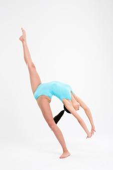 Jeune femme, faire, acrobatie, stunt, isolé, sur, a, mur blanc
