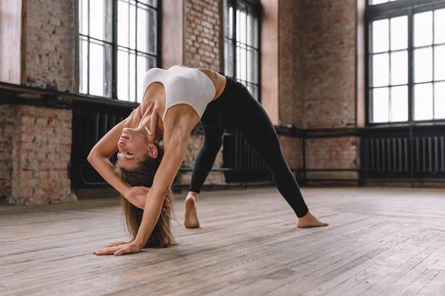 Jeune femme, faire, complexe, de, stretching, yoga