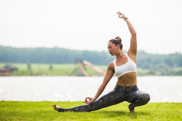 Jeune femme faire du yoga pose au parc le matin avec la lumière du soleil