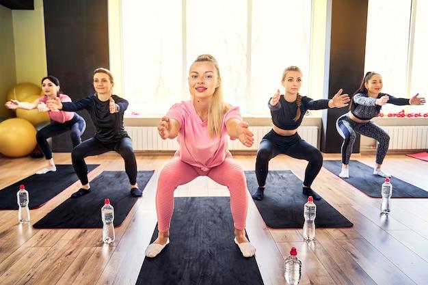 Jeune femme, faire, squat, exercice, à, groupe, formation fitness