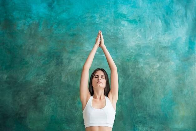 Jeune femme, faire, yoga, exercices, sur, mur vert