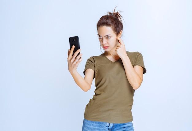 Jeune femme faisant un appel vidéo en ligne et a l'air réfléchie