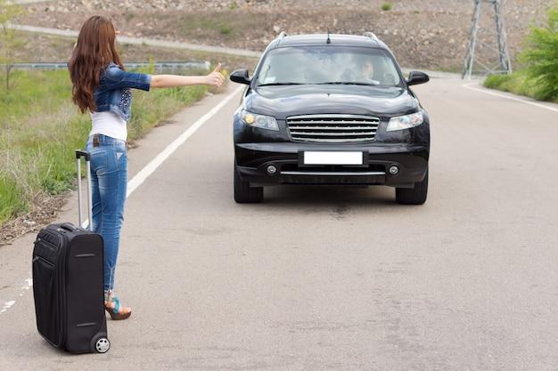 Jeune femme faisant de l'auto-stop avec une valise