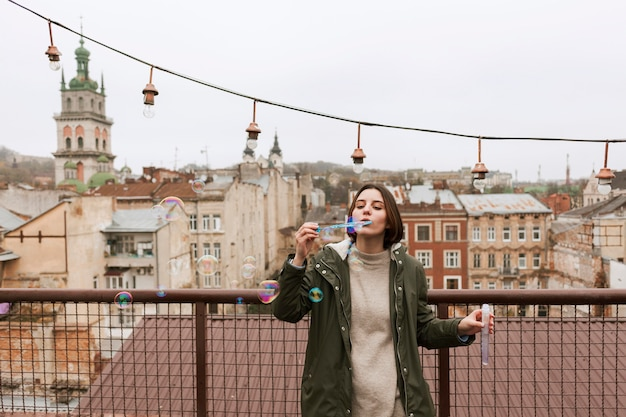 Jeune femme faisant des bulles de savon