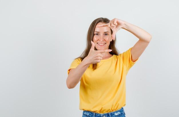 Jeune femme faisant cadre avec les doigts en t-shirt, short et à la joyeuse