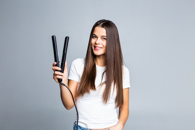 Jeune femme faisant la coiffure avec un fer à lisser isolé sur gris