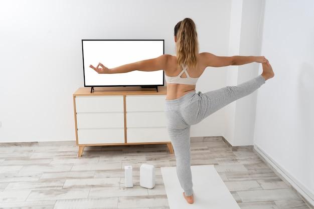 Jeune femme faisant un cours de yoga en ligne sur sa télévision vierge