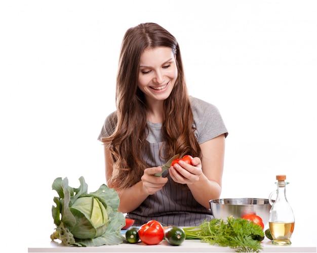 Jeune femme faisant la cuisine dans la cuisine. alimentation saine - salade de légumes. régime. concept de régime.