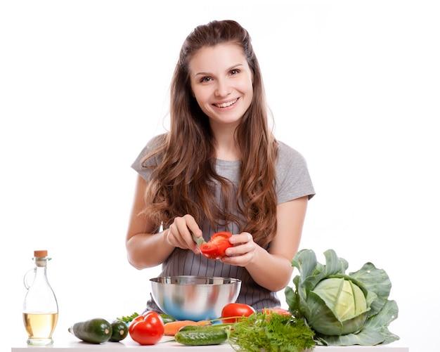 Jeune femme faisant la cuisine dans la cuisine. alimentation saine - salade de légumes.