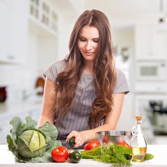 Jeune femme faisant la cuisine dans la cuisine. la nourriture saine