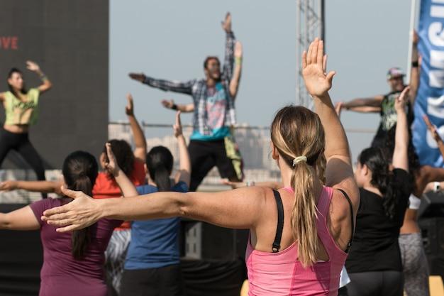 Jeune femme faisant du fitness avec un entraîneur en plein air