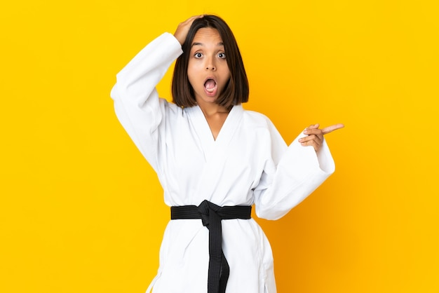Jeune femme faisant du karaté isolé sur fond jaune surpris et pointant le doigt sur le côté