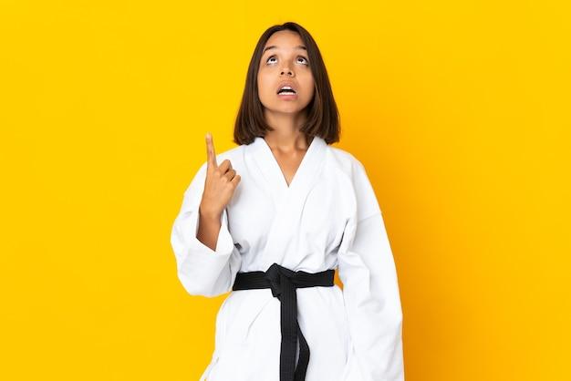 Jeune femme faisant du karaté isolé sur un mur jaune pointant vers le haut et surpris