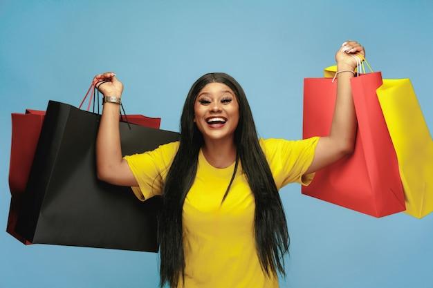 Jeune femme faisant du shopping avec des packs colorés sur mur bleu