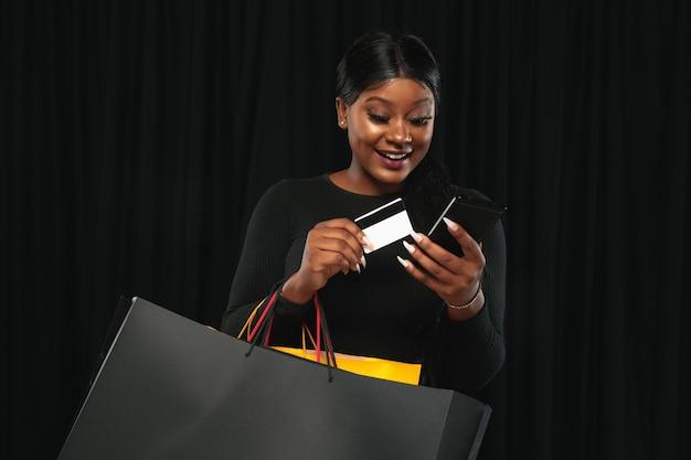 Jeune femme faisant du shopping avec des packs colorés sur mur noir
