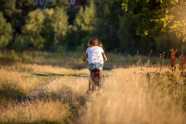 Jeune femme faisant du vélo au pré sur le chemin de terre
