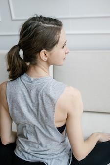 Jeune femme faisant du yoga assis dans l'exercice à la maison