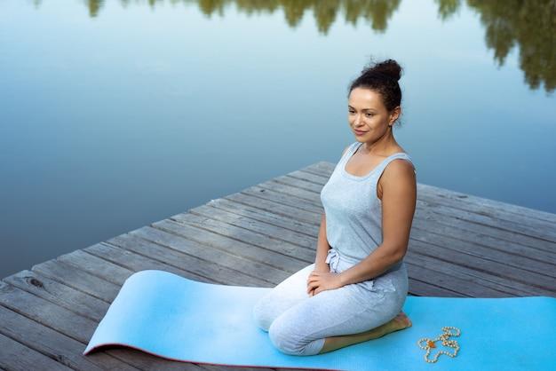 Jeune femme faisant du yoga au bord du lac