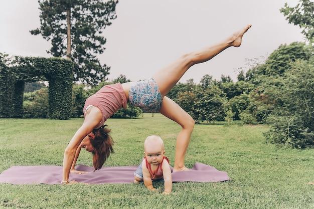 Jeune femme faisant du yoga avec bébé dans le parc d'été