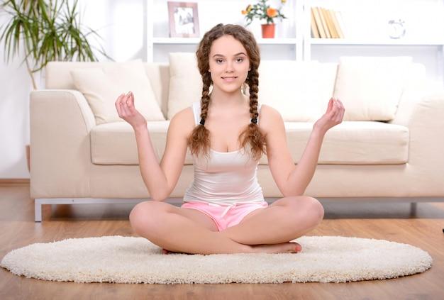 Jeune femme faisant du yoga dans la chambre à la maison.