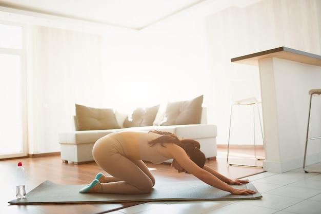 Jeune femme faisant du yoga dans la chambre pendant la quarantaine. asseyez-vous sur le tapis et étirez le dos et les bras dans la pose de yoga de l'enfant. détente après l'entraînement.