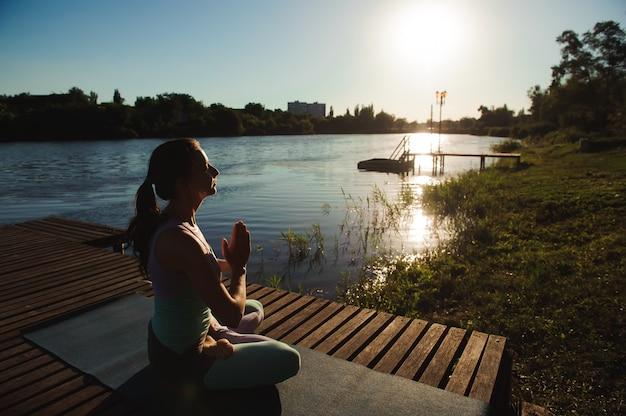 Jeune femme faisant du yoga dans le parc du matin près du lac.