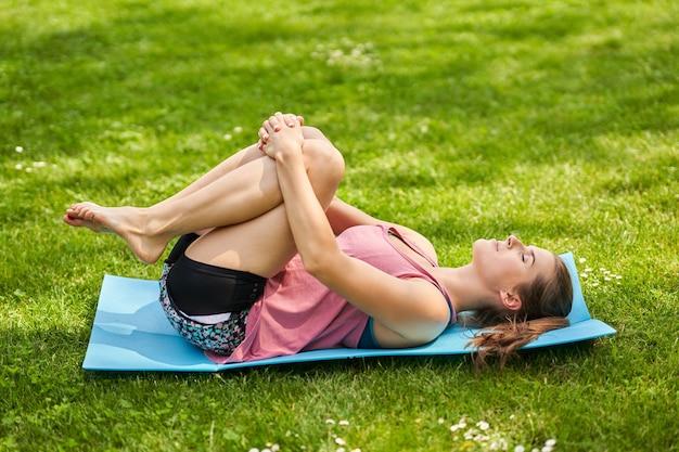 Jeune femme faisant du yoga dans le parc du matin