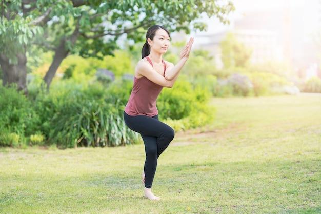 Jeune femme faisant du yoga dans un parc verdoyant sur une belle journée