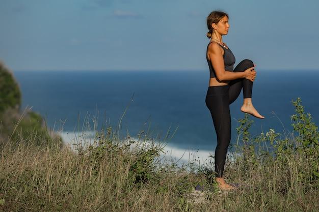 Jeune femme faisant du yoga à l'extérieur avec une vue arrière incroyable. bali. indonésie.