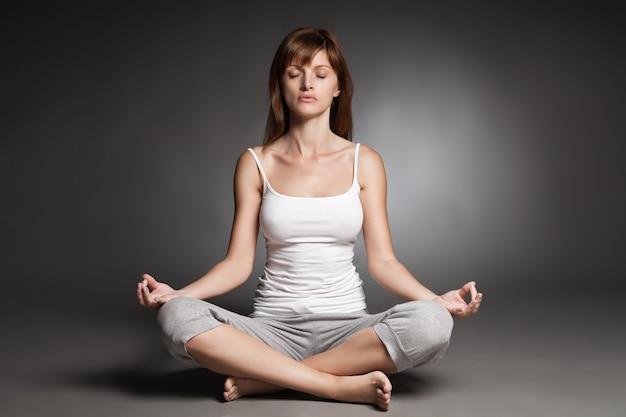 Jeune femme faisant du yoga sur fond sombre