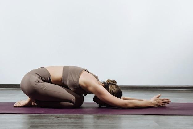 Jeune femme faisant du yoga à l'intérieur sur le tapis faisant la pose de relaxation