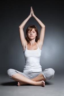 Jeune femme faisant du yoga isolé sur fond sombre
