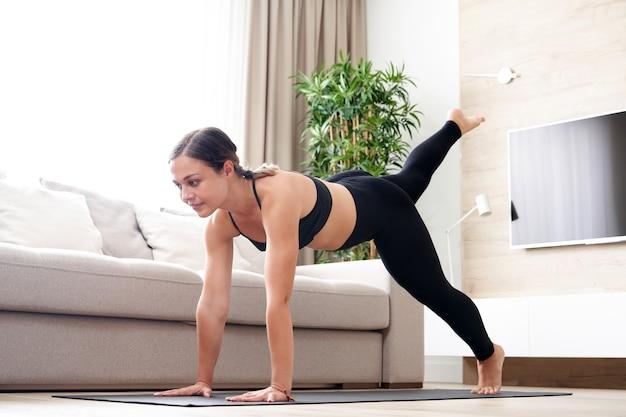 Jeune femme faisant du yoga planche à la maison dans le salon mode de vie sain et concept de régime alimentaire