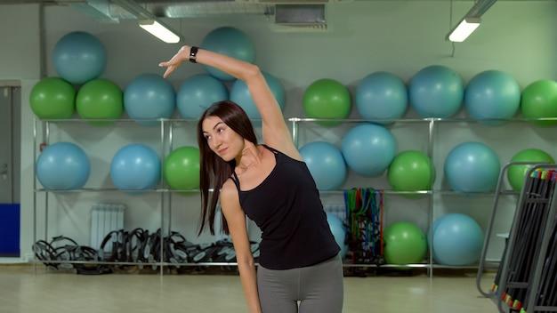 Jeune femme faisant l'échauffement avant de s'entraîner dans le concept de gym d'un mode de vie sain